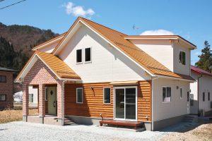 木の温もりに包まれた オレンジ色の三角屋根の家